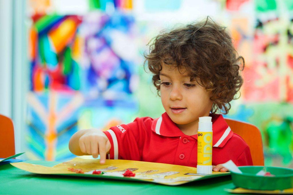 Foto eines kleinen Kindes an der Swiss International Scientific School in Dubai, das die Frage aufwirft, wie Eltern während einer Pandemie die beste Schule für jüngere Kinder wählen, wenn es fast unmöglich ist, Schulen zu besuchen oder sie normal arbeiten zu sehen.