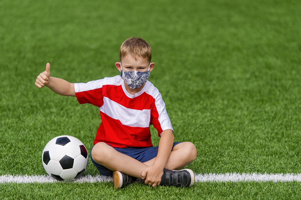 Sport during Covid at GEMS schools. Photograph shows a child enjoying football even with the restrictions.