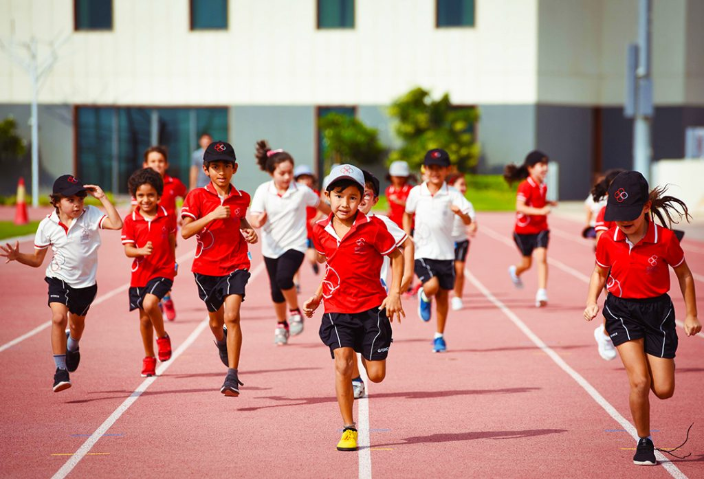 Kinder der Swiss International Scientific School rennen während der Atheltik im Rahmen des Sportfokus der Schulfracht zu BTEC-Optionen im IB CrP um die Ziellinie