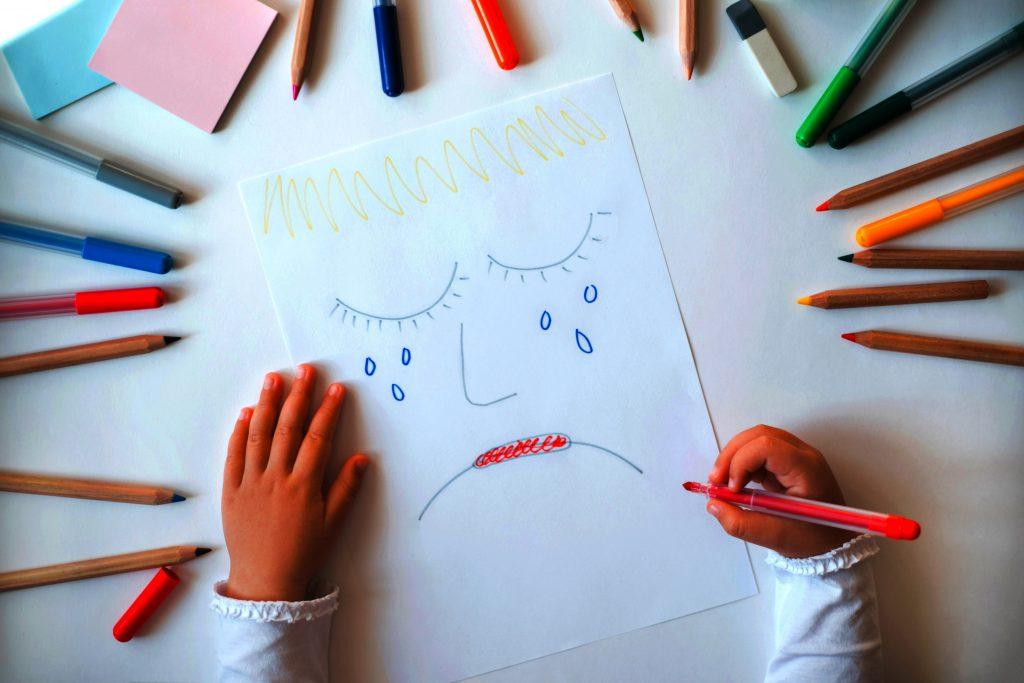 Kind, das durch Trauerverlust und Trauer durch Zeichnen und nicht durch Worte arbeitet.