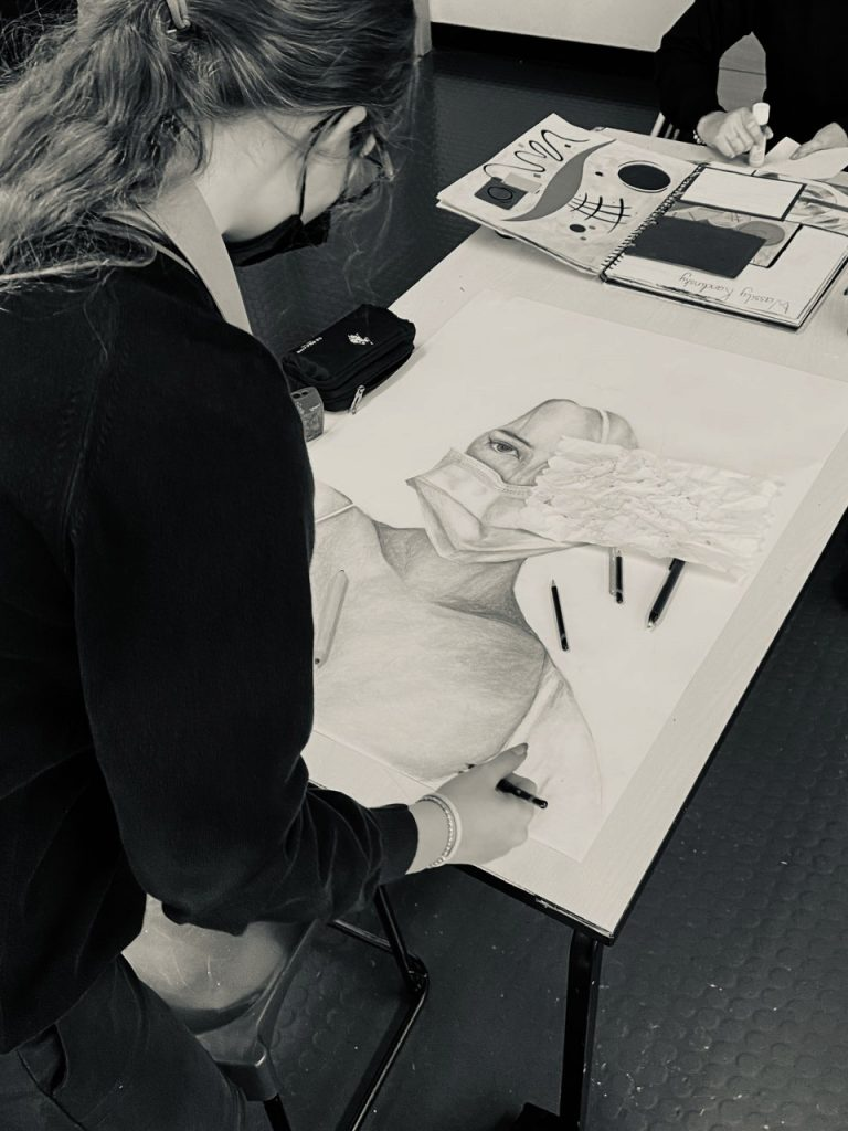 Photograph of student at the British School Al Khubaiarat working on her Junk Kouture entry 2021