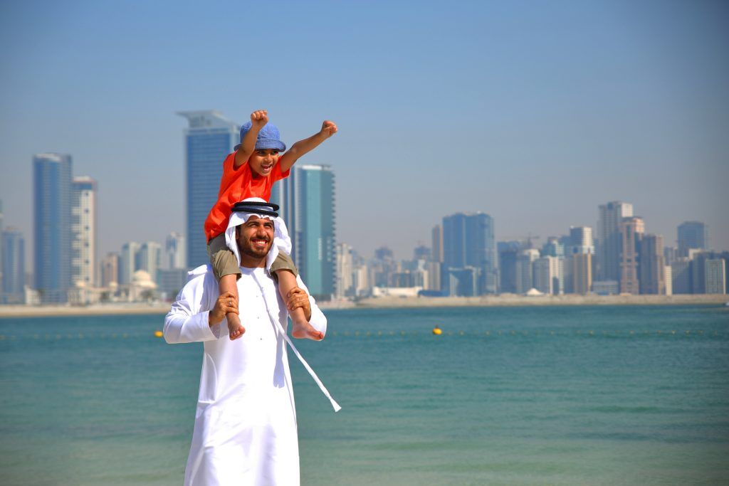 Photograph of Dad with his child having fun on the beach in Dubai in the Half Term holidays